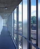 Narrow passage next to glass facade