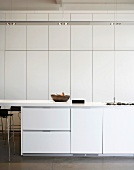 White kitchen with floor-to-ceiling fitted cupboards & recessed ceiling lamps