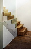 Stairwell with wooden stairs & glass balustrade