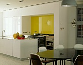 Open-plan kitchen with yellow glass wall & dining area