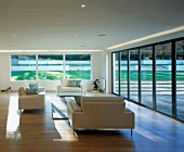 Living room with sofas, large windows & terrace doors