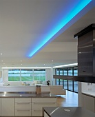 Living space with open-plan kitchen, ceiling lights & large windows