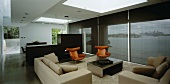 Open-plan living space with sofas, armchairs & room divider