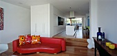 Long, open-plan living space with sofa & steps to kitchen