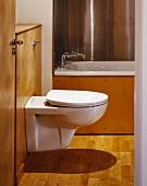 Toilet in bathroom with wood panelling & parquet floor