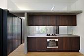 Dark wood kitchen in room with steel-clad walls