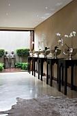 Halle mit weissen Orchideen in reflektierenden Silberschalen auf schwarzen Sockeln im chinesischen Stil