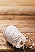 A roll kitchen twine on a wooden surface