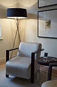 Corner of living room with standard lamp, armchair and side table