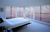 Grosse Fensterfront mit Jalousien in einem Schlafzimmer