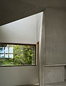Interior room with exposed concrete walls, window and view of garden