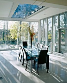 Black leather chairs at glass-topped dining table in front of glass facade