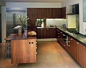 Open-plan designer kitchen with free-standing island and walnut fronts