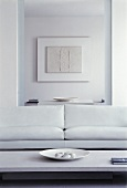 White sofa in front of open doorway to dining room