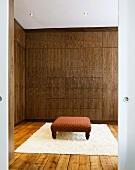 Antiker gepolsterter Fussschemel auf hellem Teppich vor Schrank in Ankleide