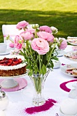 Pink ranunculus and strawberry cake on table set for afternoon tea