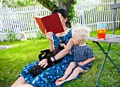 Mother and daughter sitting on lawn in garden
