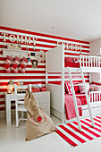 White bunk beds against red and white striped wall with matching rug in children's bedroom
