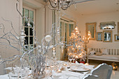 Festively set table in front of illuminated Christmas tree in white living-dining room
