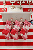Christmas stockings hanging from bracket shelf on red and white striped wall