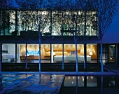 Courtyard with trees in front of contemporary house at dusk with view into illuminated interior