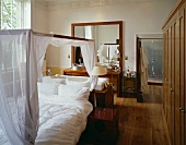 Four-poster bed with white hangings in front of bathtub and washstand in bedroom