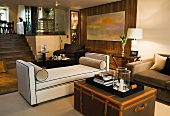 Tray on antique trunk in front of light upholstered couch in modern, split-level living space
