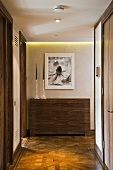 Hallway with modern wood panelling over radiators and old parquet flooring