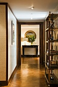 Chrome shelving in hallway and view of console table through ceiling-height door