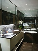 Designer bathroom with two sinks in washstand and black-tiled walls and bathtub