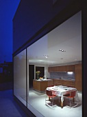 Modern house at twilight with view of dining area in illuminated kitchen