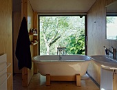 Free-standing bathtub in front of floor-to-ceiling window with view of garden