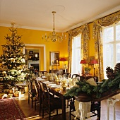 Festive, set dining table and Christmas tree in yellow-painted dining room