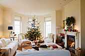 Light sofa set in traditional interior with Christmas tree in window bay