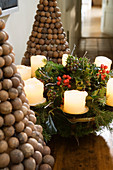 Christmas wreath with white candles and ornamental fir trees made of wooden balls