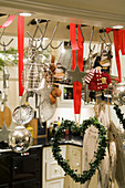 Heart-shaped wreath hanging on hook next to kitchen utensils