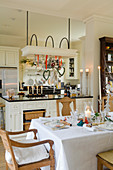 Set dining table in open-plan country house kitchen