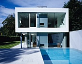 Pool area of two-storey, box-shaped house in glass and concrete