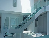 Glass staircase leading from dining room to upper storey