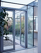 Glass doors and walls separate living space from garden