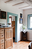 Half-height rustic cabinet with drawers next to open doorway with frame painted pale blue in farmhouse
