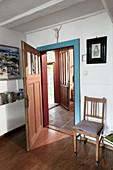 View through open interior door into hallway with tiled floor and open front door