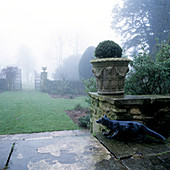 Box ball in vintage planter and stone fox statue on terrace with view into misty garden