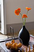 Schwarze Vase mit orangefarbenen Gerbera und antiker Drahtkorb mit Obst auf antikem Holztisch