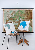 Cushions with cartographic motifs on chair and wooden swivel chair in front of map hanging on wall