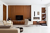 Modern living room with dark wood cladding on wall next to integrated fireplace