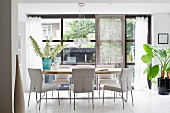 Dining area with white, upholstered chairs in front of floor-to-ceiling windows