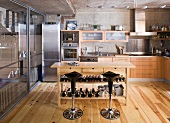 Designer kitchen with wood and stainless steel fronts; wooden table with wine rack and bar stools in centre of room
