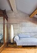 Grosser Kleiderschrank mit Spiegeltür und ein Tagesbett in einem Gästezimmer mit Betonwand