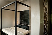 Modern canopied bed with black frame and delicately carved wooden back wall in elegant bedroom